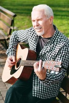 Forma do acorde. homem maduro pensativo posando no banco e tocando violão