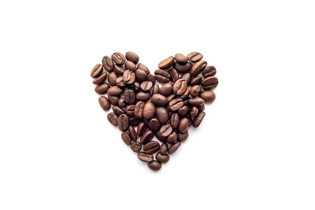 Forma do coração dos feijões de café roasted isolados em um fundo branco.