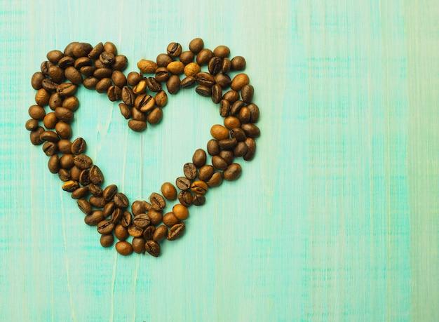 Forma do coração feita dos feijões de café na superfície de madeira.