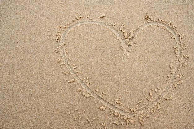 Forma do coração no fundo da areia da praia.