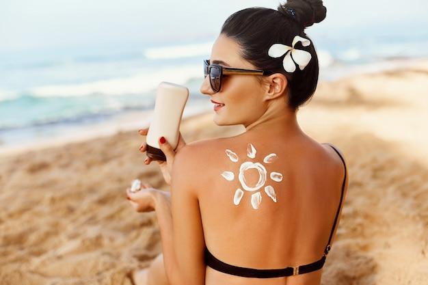 Forma do sol criada a partir de loção protetor solar nas costas da jovem