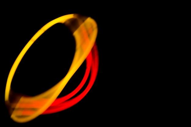 Forma oval feita com luzes amarelas e vermelhas de néon no fundo preto