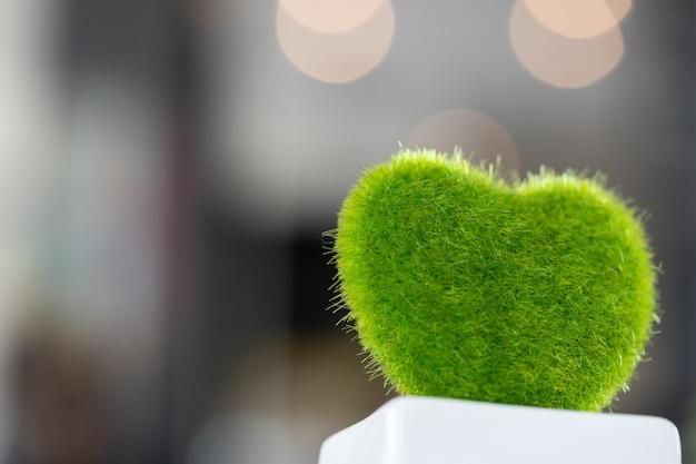 Forma verde do coração feita da grama, com luzes do bokeh de atrás.