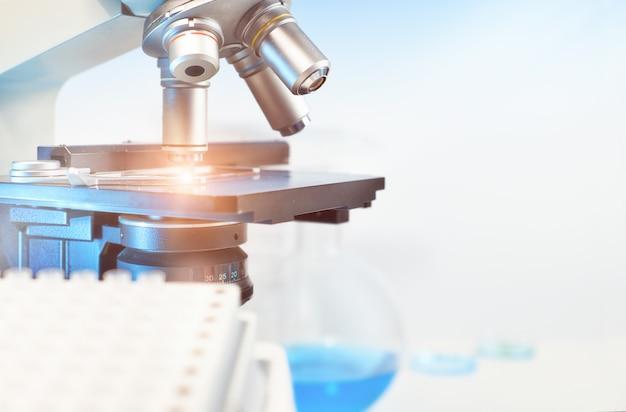 Formação científica com closeup no microscópio de luz e laboratório turva