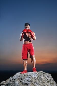 Formação de boxer masculino musculoso, olhando para a câmera ao ar livre