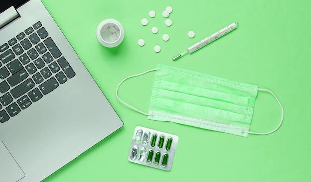 Formação médica. espaço de trabalho de um médico moderno. laptop, comprimidos, máscara facial, termômetro sobre fundo verde. vista do topo. postura plana