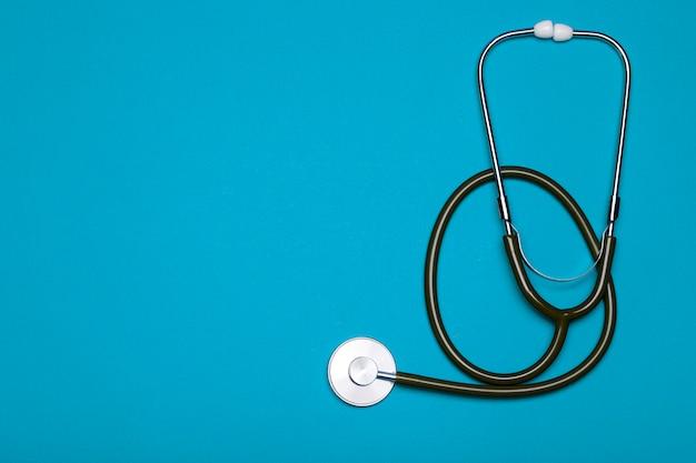 Formação médica. estetoscópio sobre um fundo azul claro. conceito de tratamento de farmacologia, clínica, saúde e doença