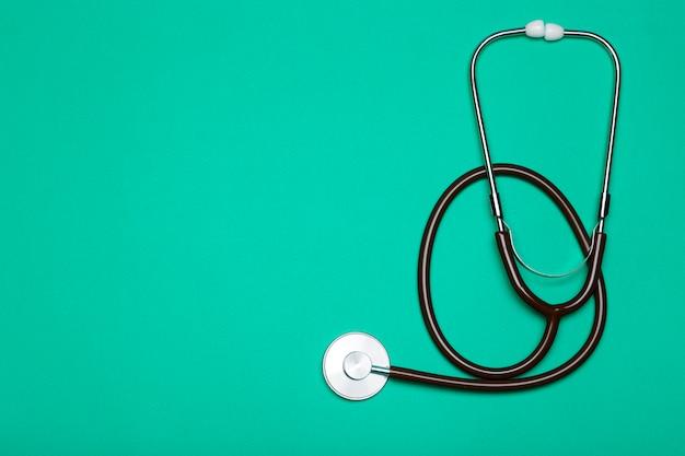 Formação médica. estetoscópio sobre um fundo verde claro. conceito de tratamento de farmacologia, clínica, saúde e doença