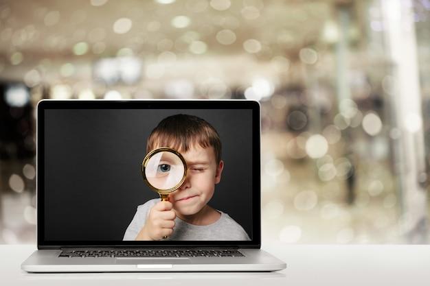Formação online através do computador portátil em casa. rosto de menino no monitor do computador