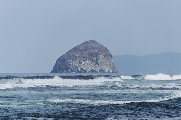 Formação rochosa cinza no mar durante o dia