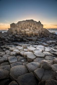 Formação rochosa curiosa com segmentos hexagonais ao lado de um corpo de água