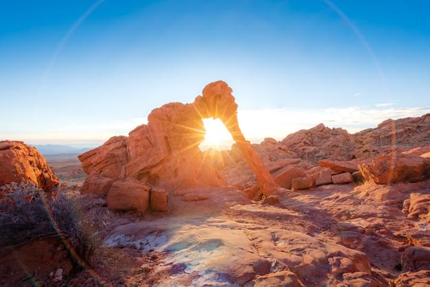 Formação rochosa de elefante com o nascer do sol e raio de sol no vale do fogo
