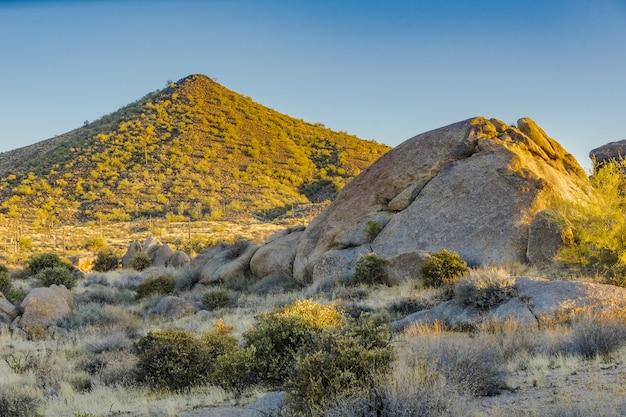 Formação rochosa iluminada pelo sol e uma montanha deserta na luz do amanhecer sob um céu claro