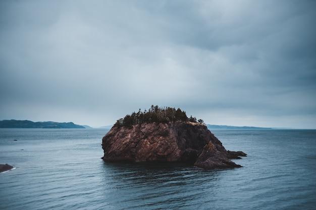 Formação rochosa marrom no mar azul sob nuvens brancas durante o dia