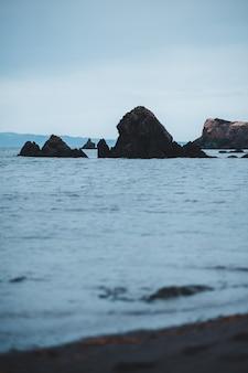 Formação rochosa marrom no mar durante o dia