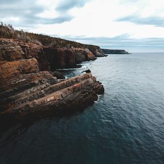 Formação rochosa marrom no mar sob nuvens brancas durante o dia