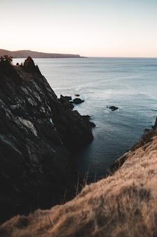 Formação rochosa marrom perto do corpo de água durante o dia