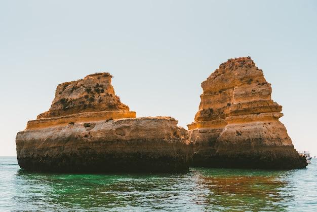 Formações rochosas refletindo no mar durante o dia