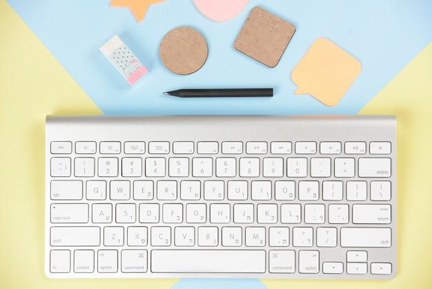 Formas; borracha e lápis perto do teclado branco em duplo cenário
