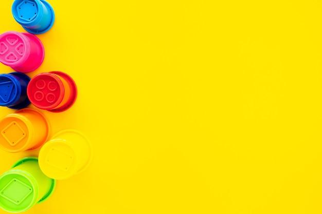 Formas de arco-íris multicoloridas para areia em um fundo amarelo. fundo de bebê brilhante, vista plana leiga, vista superior, copie o espaço para o texto.