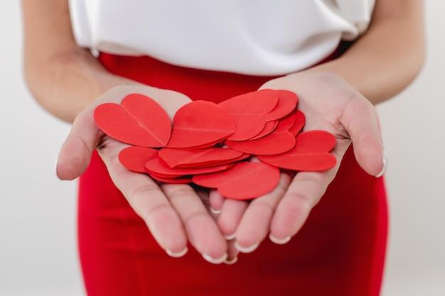 Formas de coração nas mãos da mulher negra elegante isolada