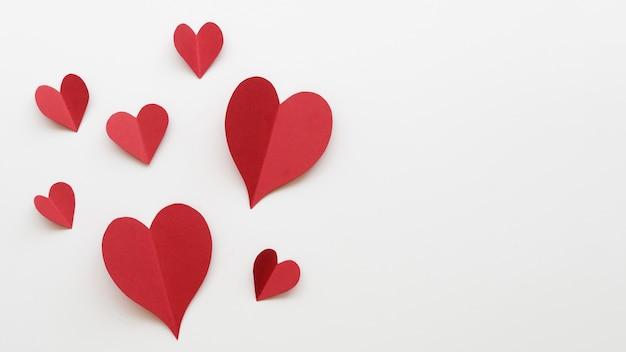 Formas de corações vermelhos de cópia-espaço na mesa