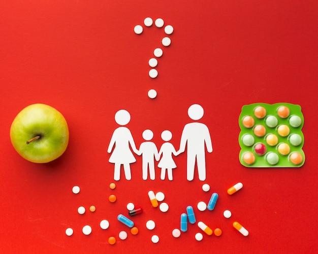 Formas de família de papelão com pílulas e alimentos saudáveis