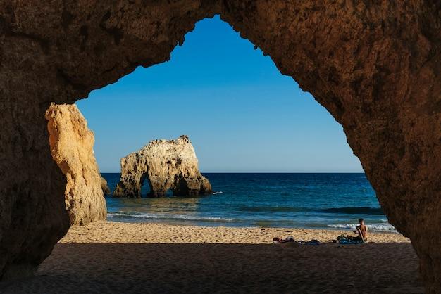 Formas de rocha e shilouettes na praia dos três irmãos no algarve, portimão, portugal
