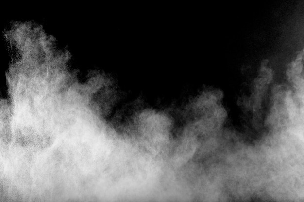 Formas estranhas da nuvem branca da explosão do pó contra o fundo preto. respingo das partículas de poeira branca.