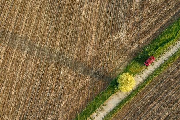 Formas geométricas abstratas de solo agrícola sem semeadura, separadas diagonalmente por estrada e carro vermelho sobre ela, nas cores verde e preto. uma visão aérea do drone.