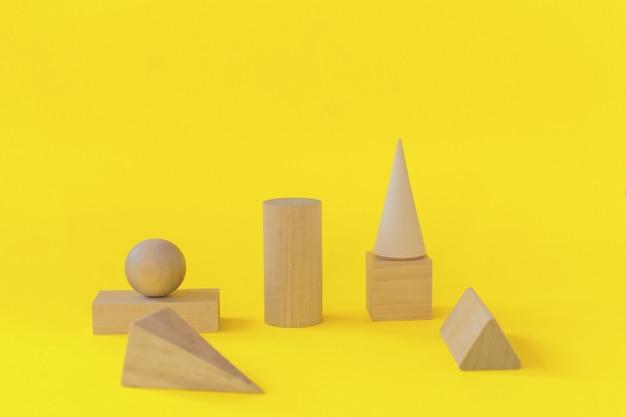 Formas geométricas de madeira em um fundo amarelo. aprendizagem pré-escolar.