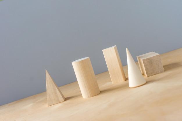Formas geométricas de madeira em um fundo cinza com espaço de cópia. aprendizagem pré-escolar.