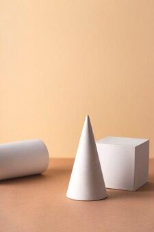 Formas geométricas em branco - um cilindro, um cubo e um cone