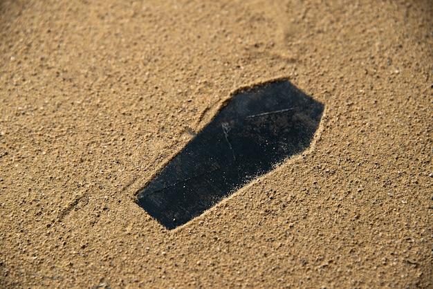 Formato de caixão preto feito na areia