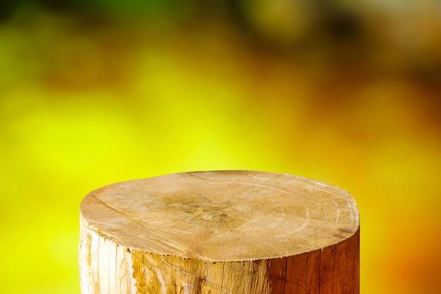Formato de cilindro redondo de serra de madeira cortado para exposição de produto com fundo abstrato de luz amarela