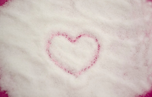 Formato de coração desenhado em fundo de açúcar granulado branco