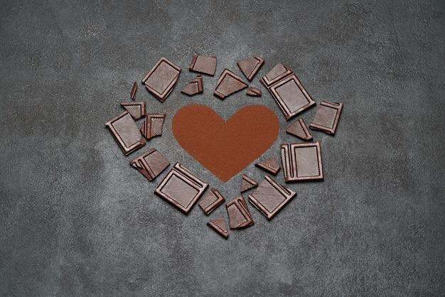 Formato de coração feito de café moído ou cacau em pó e pedaços de barra de chocolate no fundo de concreto