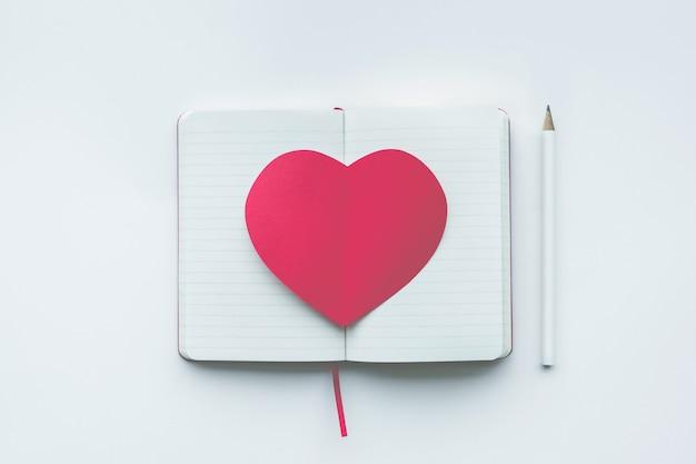 Formato de coração vermelho no bloco de notas branco