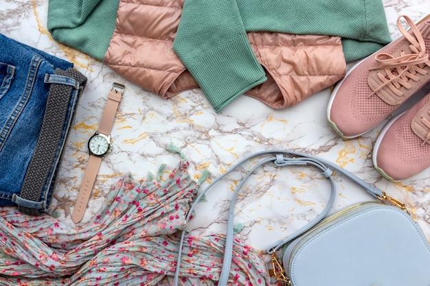 Forme a roupa das mulheres, acessórios na moda ajustados no fundo de mármore.