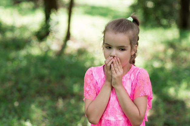 Forme o retrato da menina à moda que sorri e que levanta na câmera. andando no parque no verão.