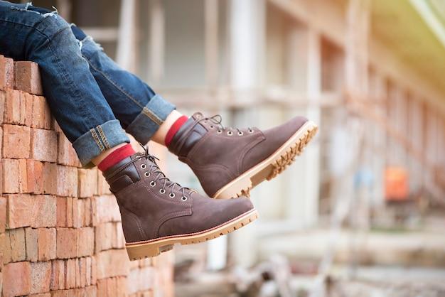 Forme os pés dos homens nas calças de brim e nas botas marrons para a coleção do homem.