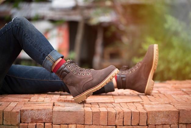 Forme os pés dos homens nas calças de brim e no couro marrom das botas para a coleção do homem.