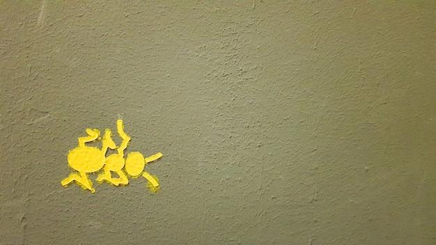 Formiga pintada de amarelo em uma parede cinza. formiga escalando uma parede. planos de fundo coloridos de formigas. artistas locais decoram as paredes das ruas.