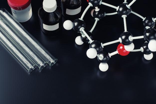 Fórmula molecular e equipamento de laboratório em um fundo escuro. conceito de química orgânica de ciência