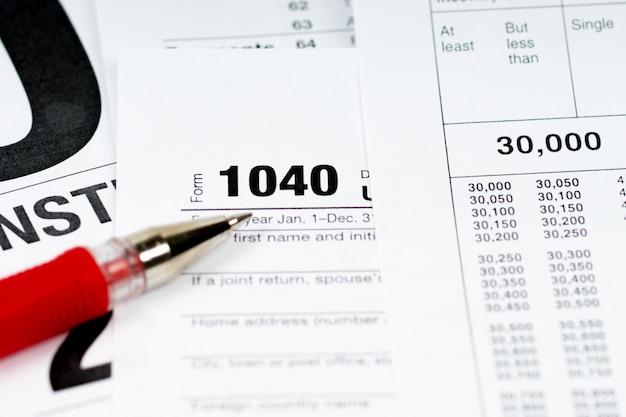 Formulário 00 com tabelas de imposto e caneta vermelha