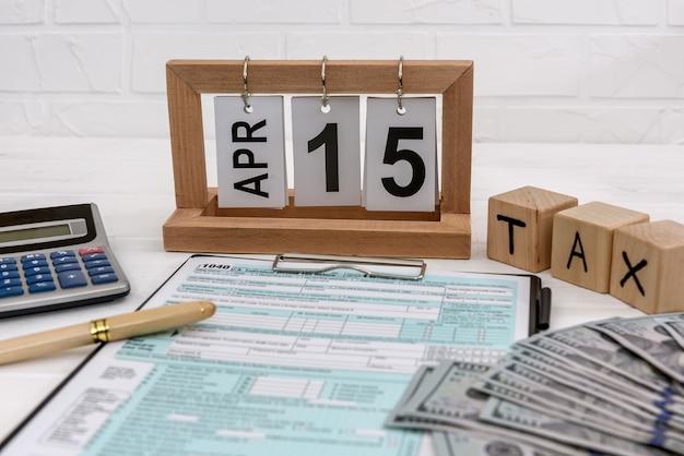 Formulário 1040 com calendário de madeira, dólar e calculadora