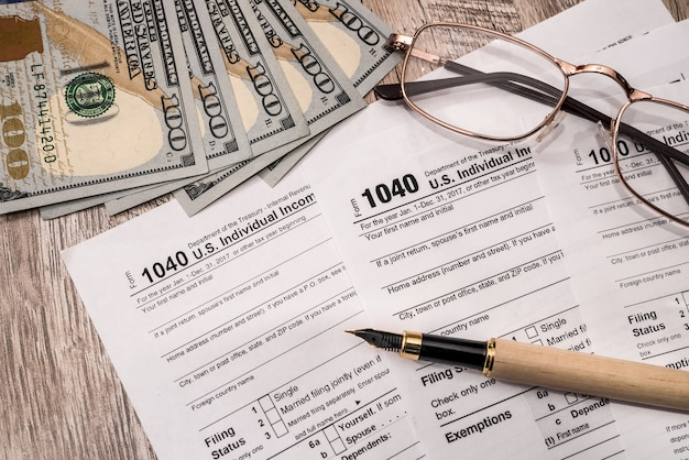 Formulário 1040 com dólar, óculos e caneta
