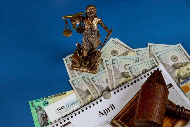 Formulário 1040 declaração de imposto de renda individual dos eua sobre o organizador do calendário, cem notas de dólar dos eua em uma mesa com martelo e escala em