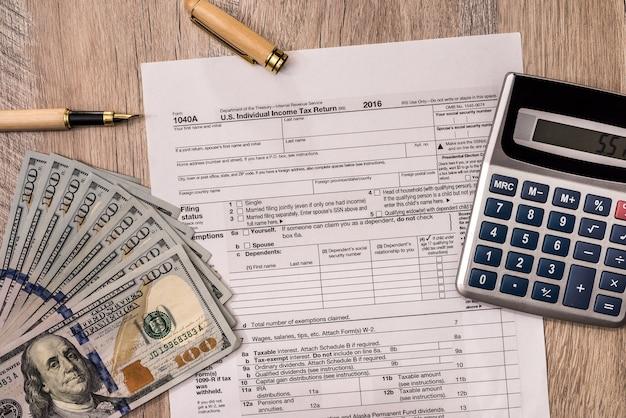 Formulário 1040, notas de dólar com calculadora e caneta