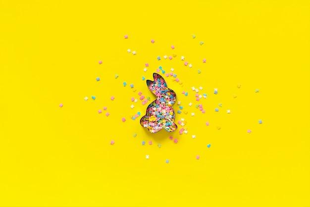 Formulário da forma do coelhinho da páscoa e cobertura de espalhamento dos confeitos que veste-se no papel amarelo.